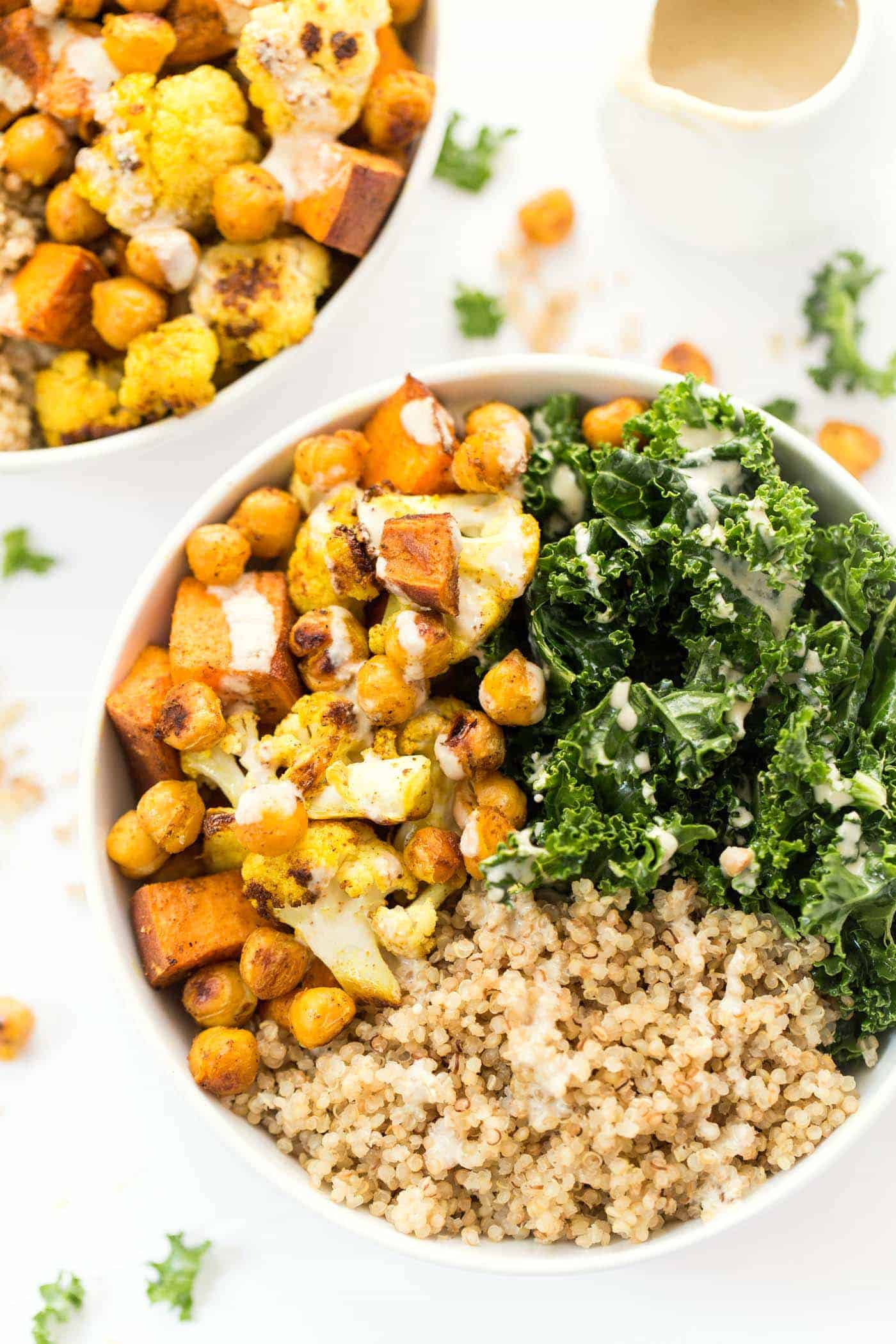 Curry Roasted Vegetable Quinoa bowls with cauliflower, sweet potatoes, chickpeas, kale and a creamy tahini dressing!