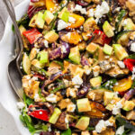 close up on a large bowl of grilled vegetable salad with tahini dressing and feta cheese