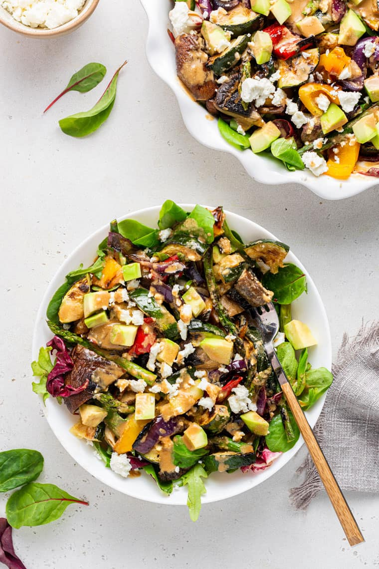 overhead of a serving of grilled vegetable salad with tahini dressing