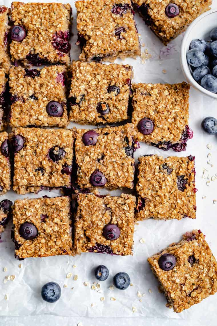 overhead of many blueberry breakfast bars on a white piece of parchment paper with fresh berries