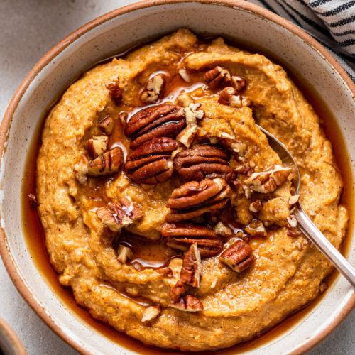 bowl of pumpkin breakfast quinoa with pecans