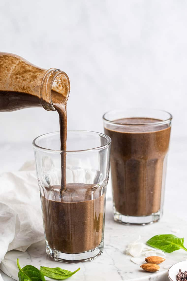 pouring an almond joy smoothie into a glass