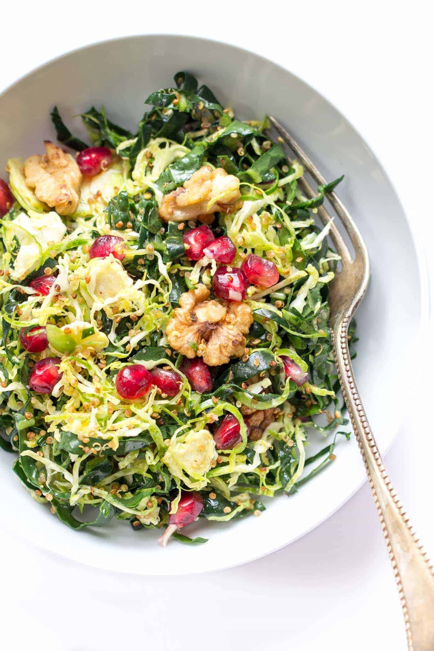 Kale + Shredded Brussels Sprout Quinoa Salad with pomegranates and toasted walnuts -- quick, easy and perfect for detoxing during the holidays!