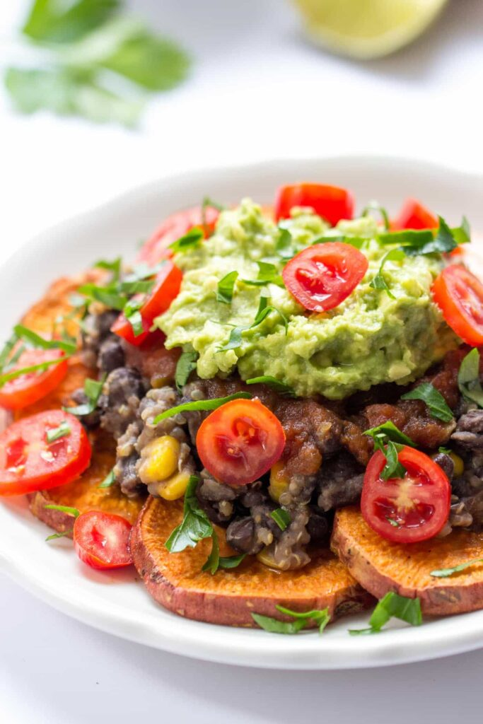 Sweet Potato Quinoa Nachos -- made with baked sweet potatoes, a black bean-quinoa mixture, salsa and topped with guac!