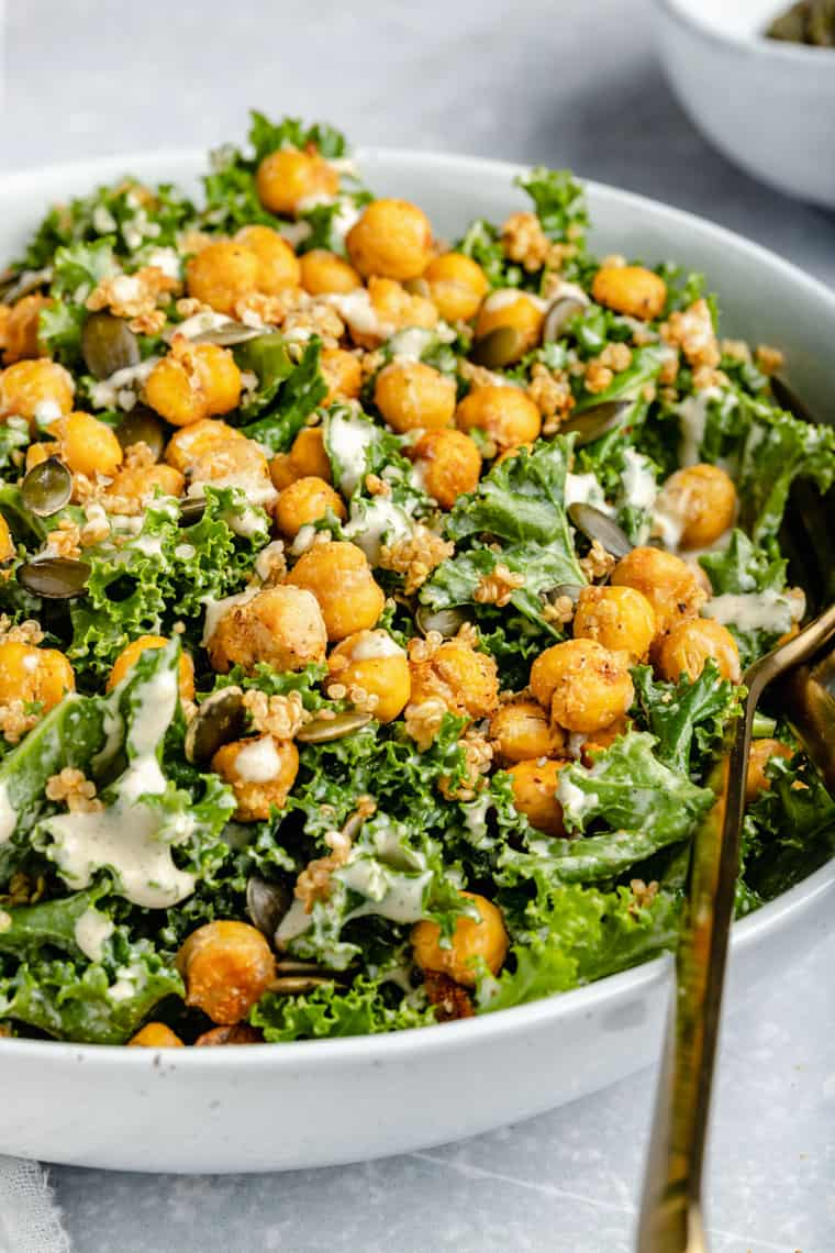 45 degree photo of a white bowl with vegan caesar kale salad with crispy chickpeas and tahini dressing