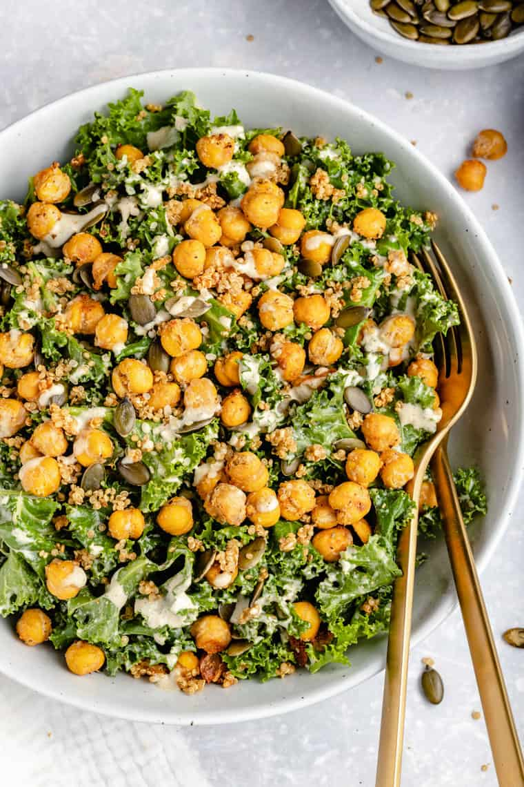 overhead of a white bowl with vegan caesar kale salad with crispy chickpeas and tahini dressing
