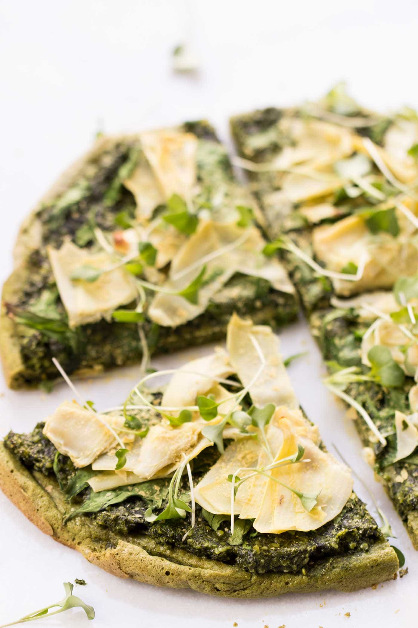 VEGAN QUINOA PIZZA...topped with pesto, spinach + artichokes, then sprinkled with nutritional yeast for a nice cheesy flavor! [gluten-free]
