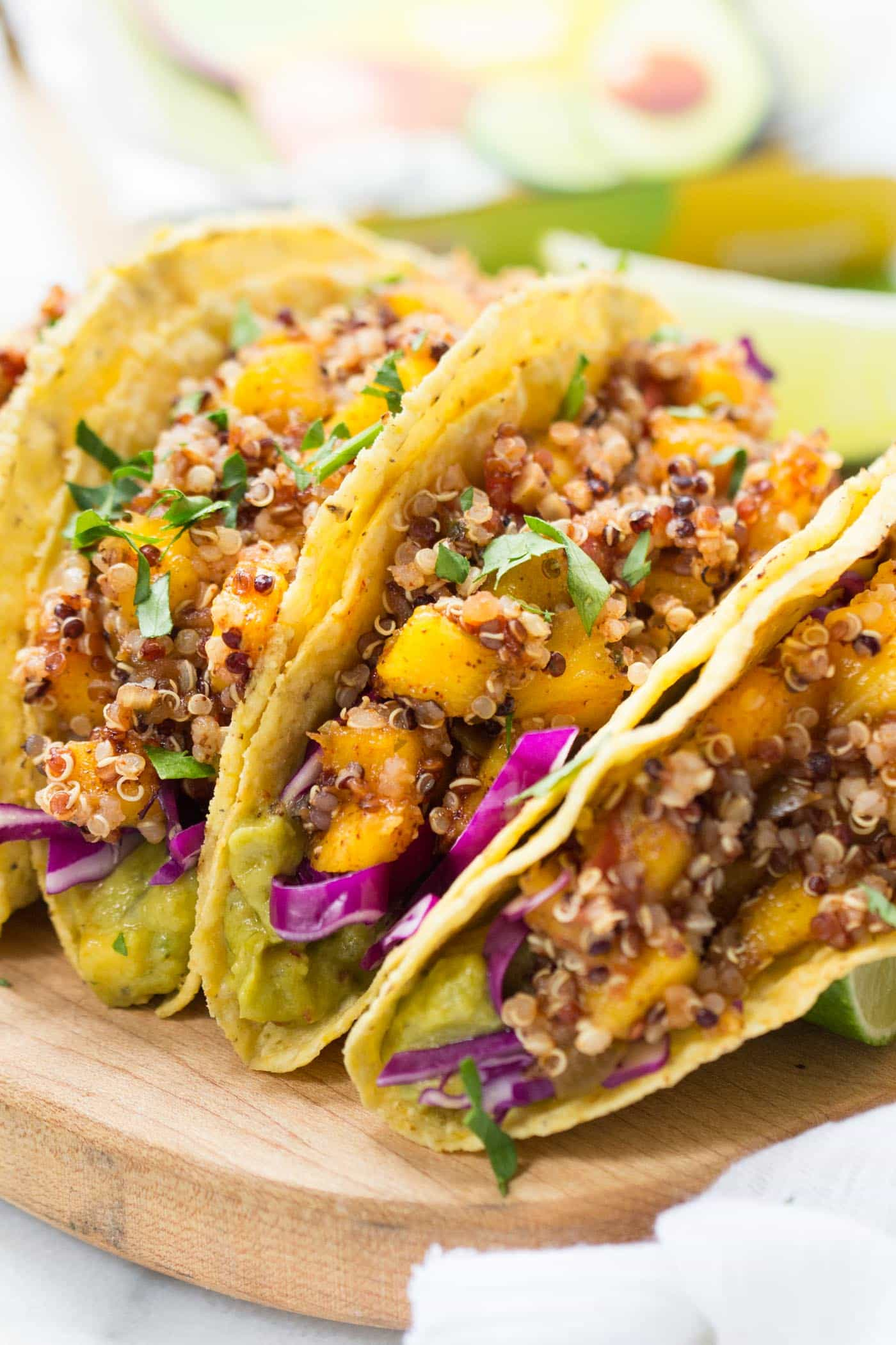 These simple Quinoa Tacos are made with a spicy mango-lime filling and use a creamy guacamole spread on the bottom!
