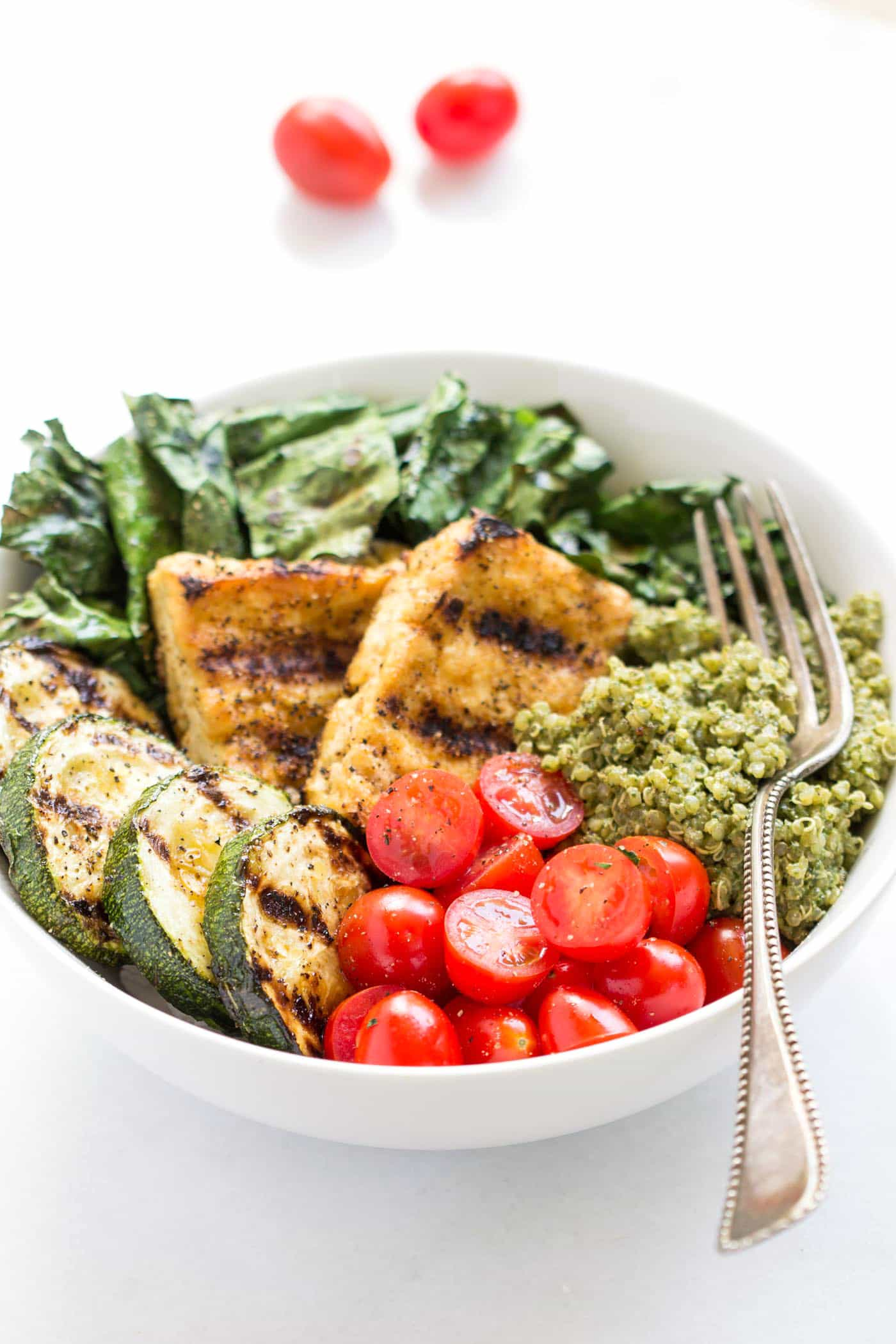 These simple pesto quinoa bowls are amazing! Topped with grilled veggies, tofu and chopped cherry tomatoes!