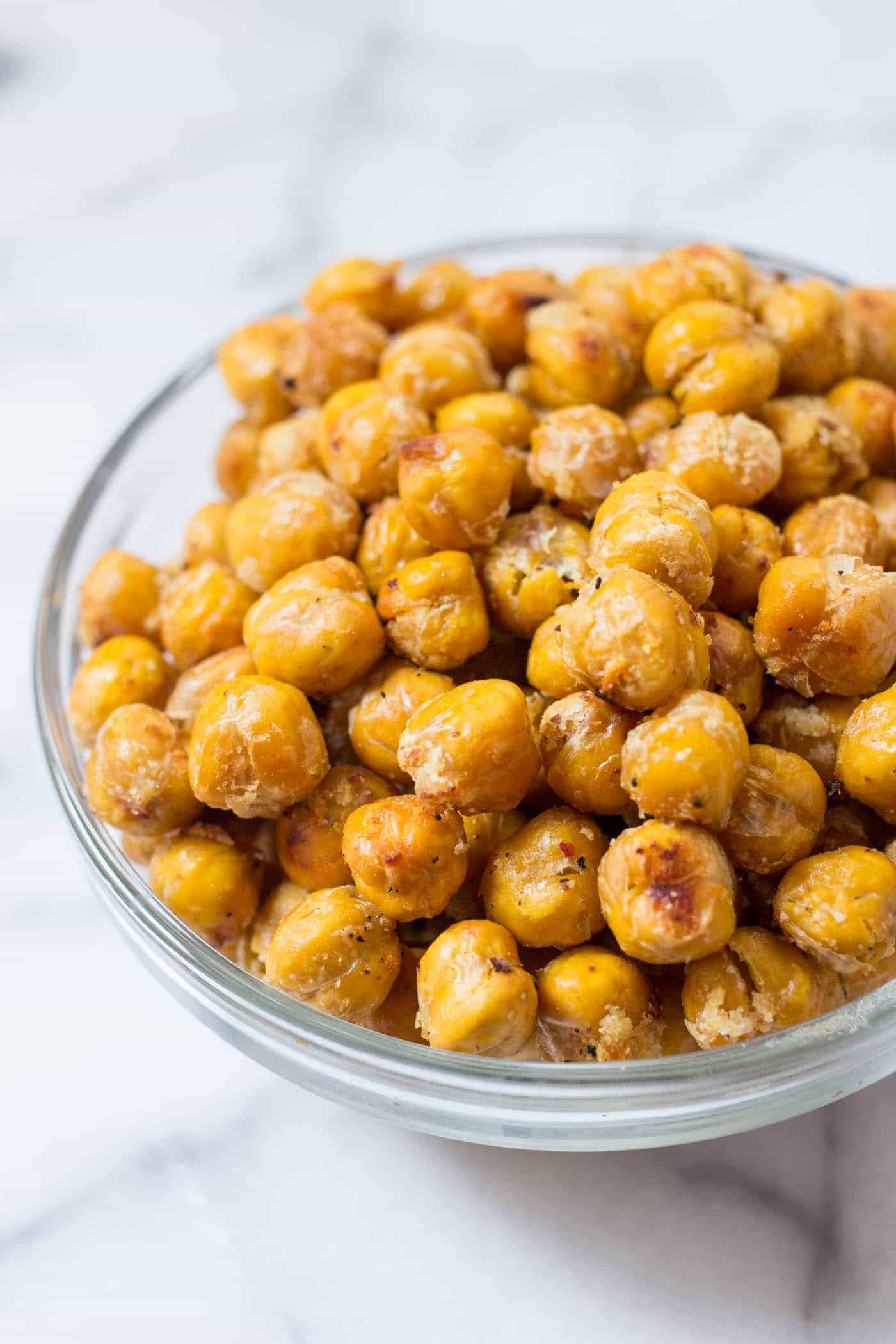 Garlicky Crispy Roasted Chickpeas -- only 5 ingredients and SO DELICIOUS. You just need chickpeas, coconut oil, garlic powder, salt + pepper....that's it!