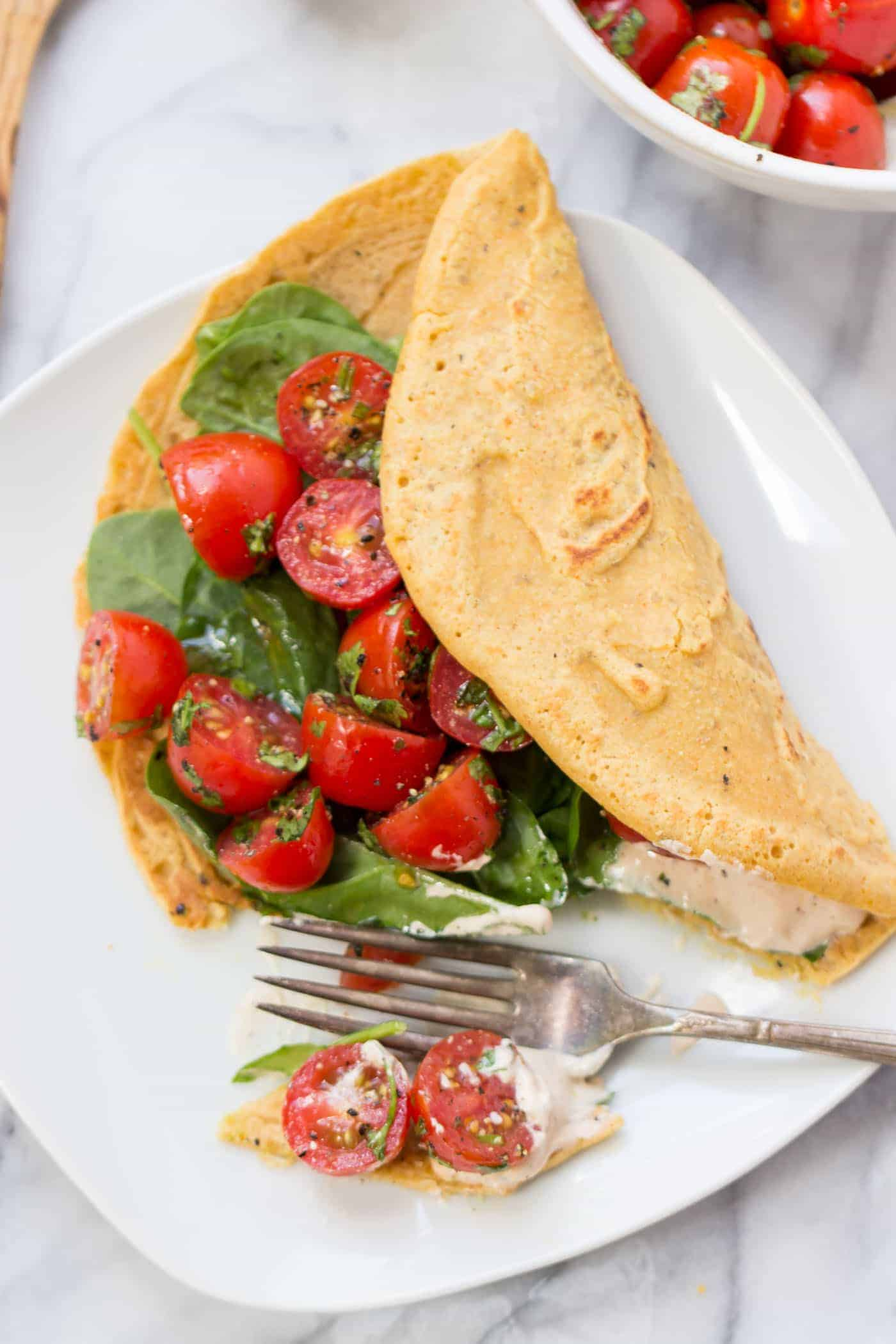 Savory Chickpea Pancakes served with a fresh tomato-cilantro salad and spinach!