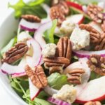 A super simple APPLE + PECAN ARUGULA SALAD topped with herbed cashew cheese and a maple-tahini dressing!