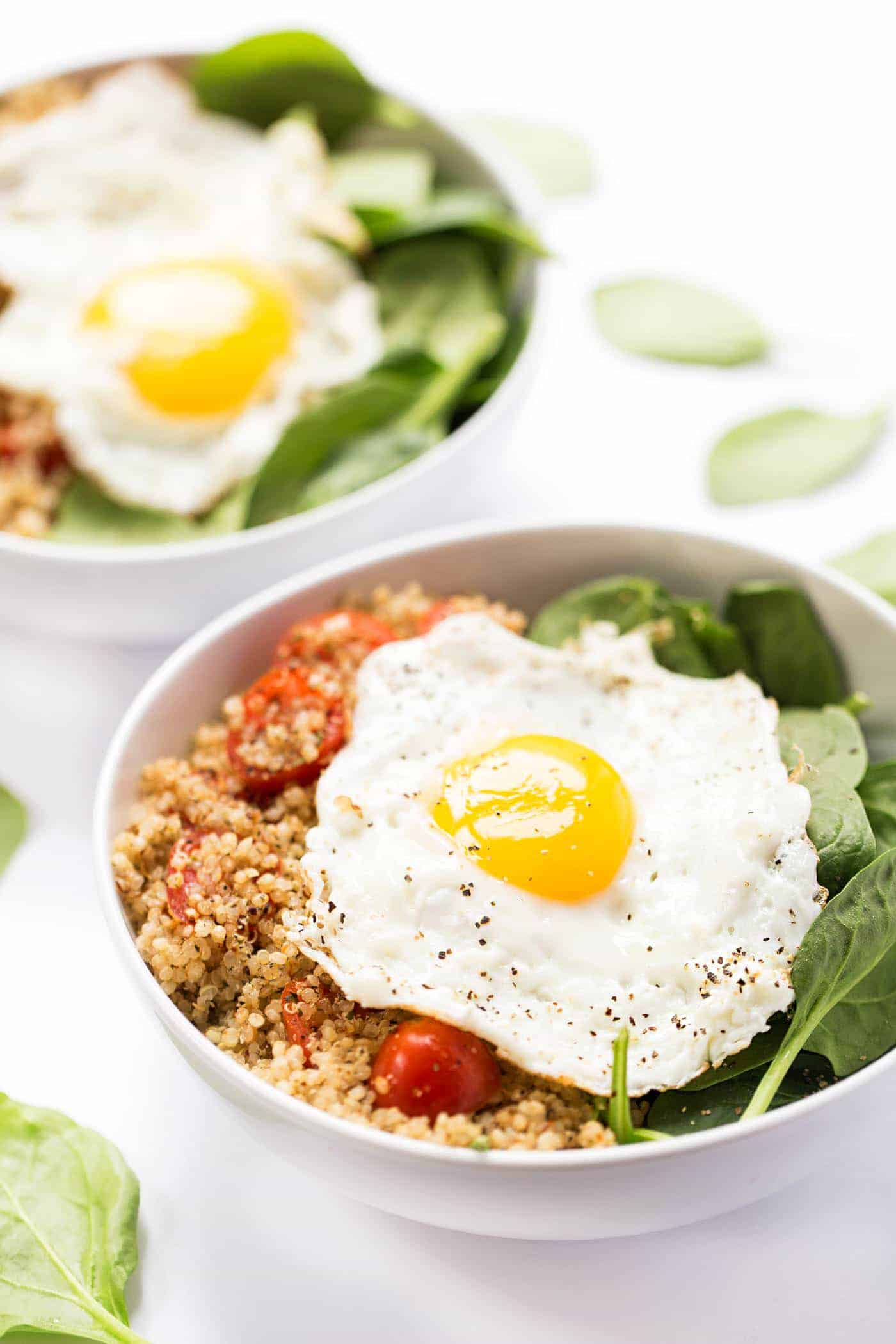 Savory Breakfast Quinoa Bowls with spinach, tomatoes and fried eggs on top!