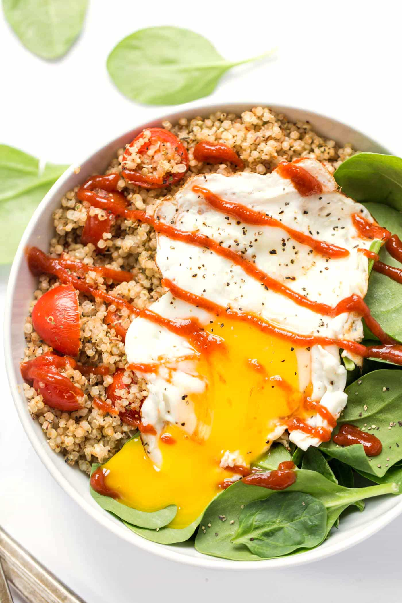These SAVORY Quinoa Breakfast Bowls -- spinach, tomatoes and fried eggs make this protein-packed breakfast!