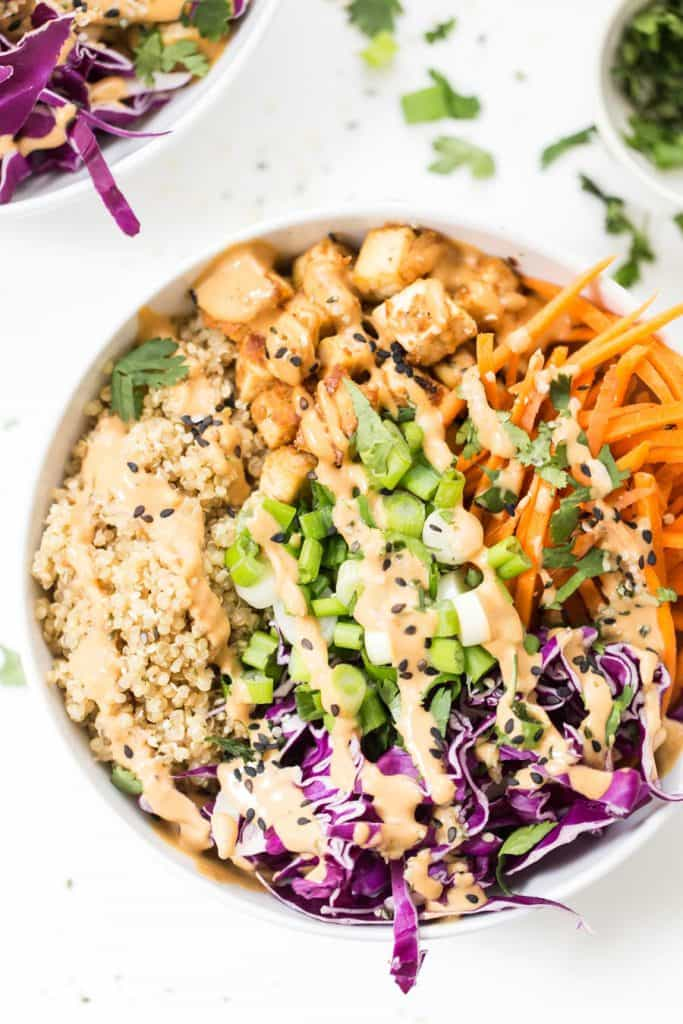 asian quinoa bowls with baked tofu and a creamy peanut sauce