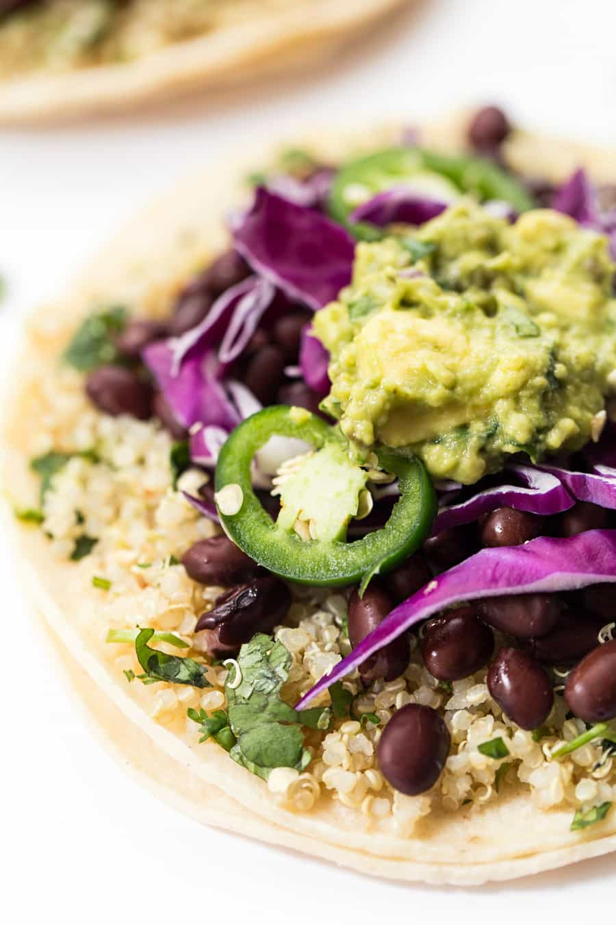 Close up on a tortilla topped with quinoa, black beans, guacamole, cabbage and peppers