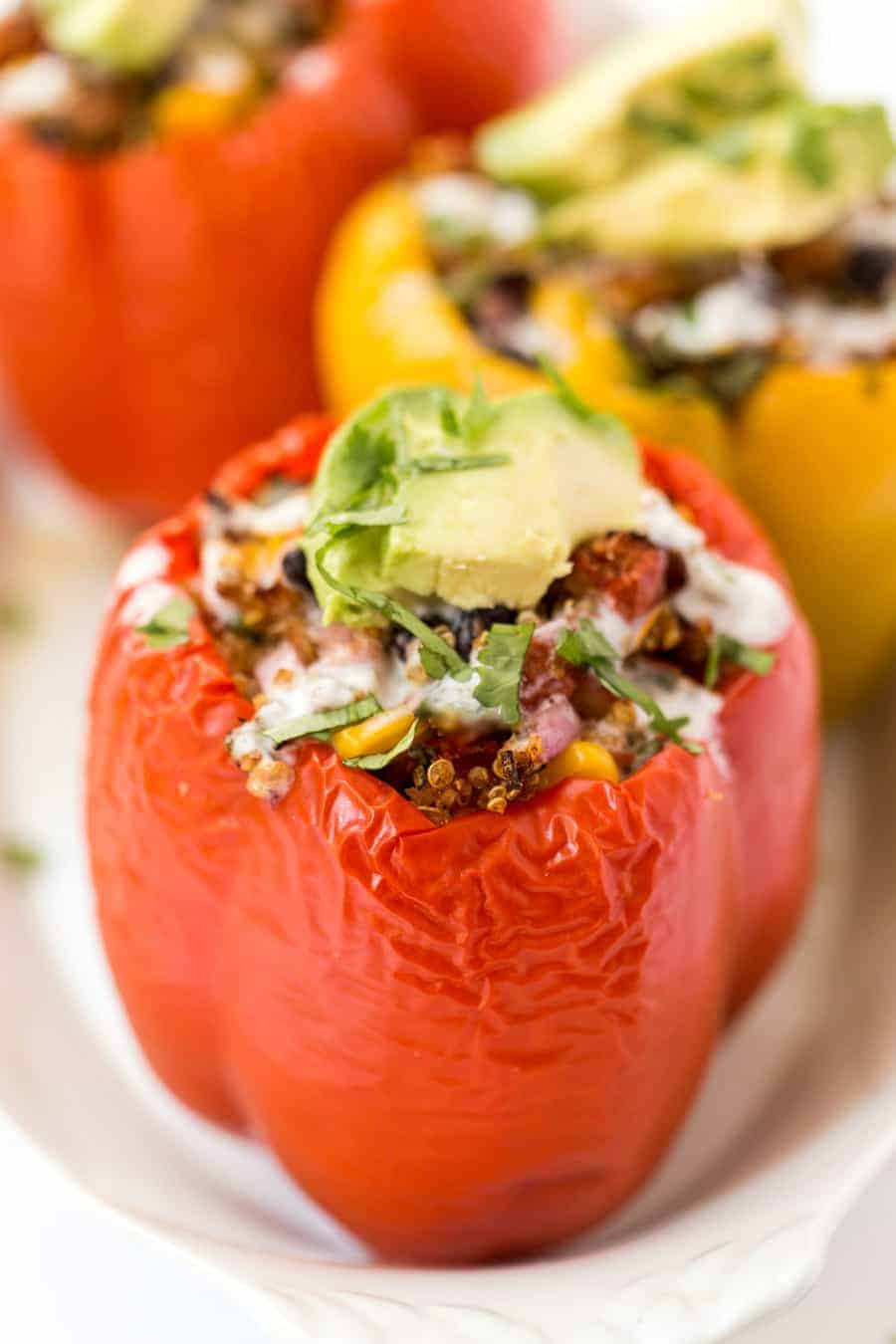 A quinoa stuffed pepper rests on a white plate.