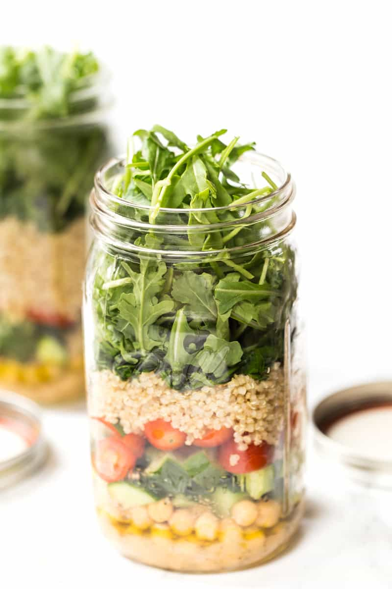 A mason jar overflowing with salad green. It also has quinoa, vegetables and chickpeas. Salad dressing fills the bottom.