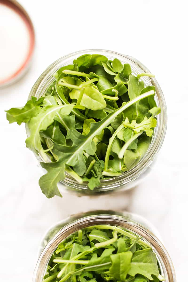 Salad greens sprout out of the top of a mason jar.
