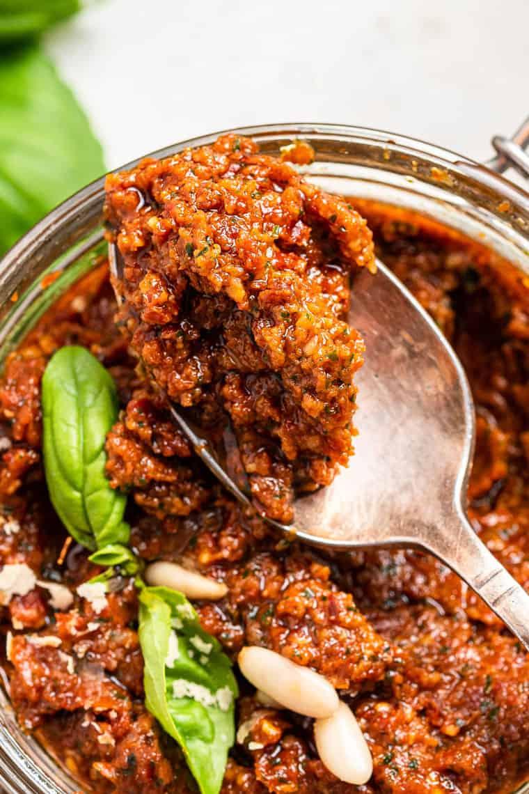 close up on a jar of sun dried tomato pesto with basil