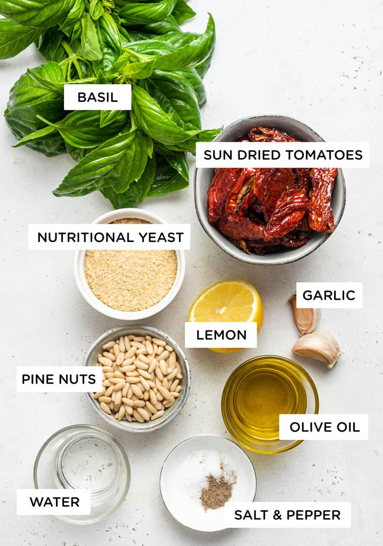 ingredients for pesto with sun dried tomatoes, garlic, lemon, olive oil, pine nuts and basil