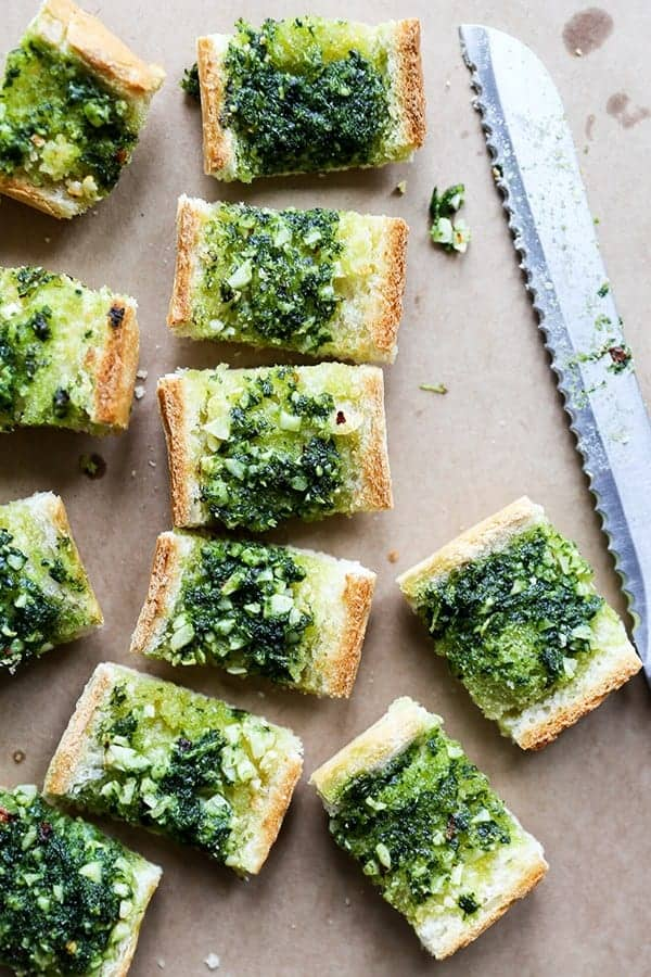vegan garlic bread topped with vegan kale pesto