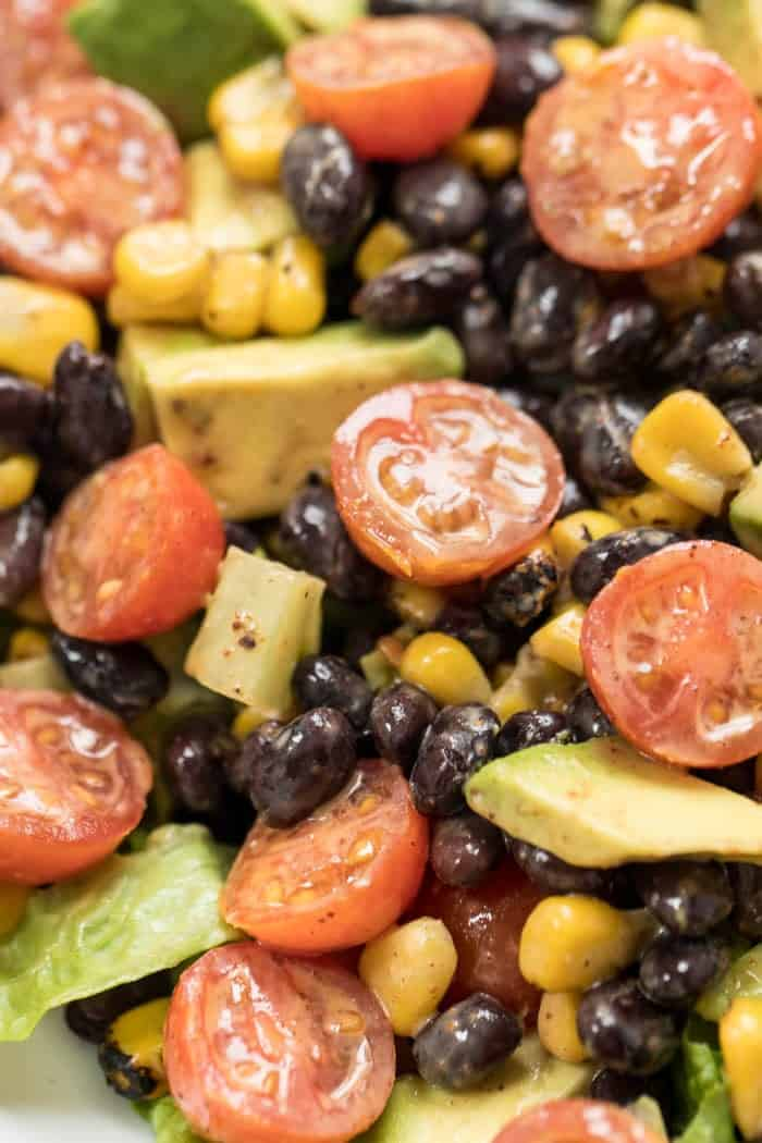 healthy taco mason jar salad with black beans, tomatoes and chili dressing