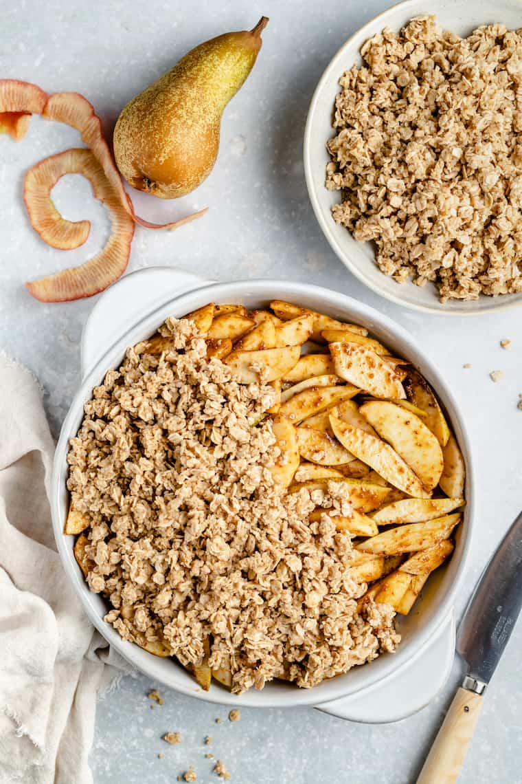assembling apple and pear crisp with oat and quinoa topping in a pie plate