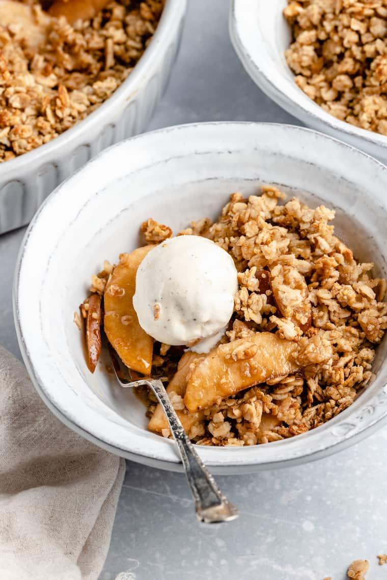 vegan apple crisp with pears and vanilla ice cream in a white ceramic bowl