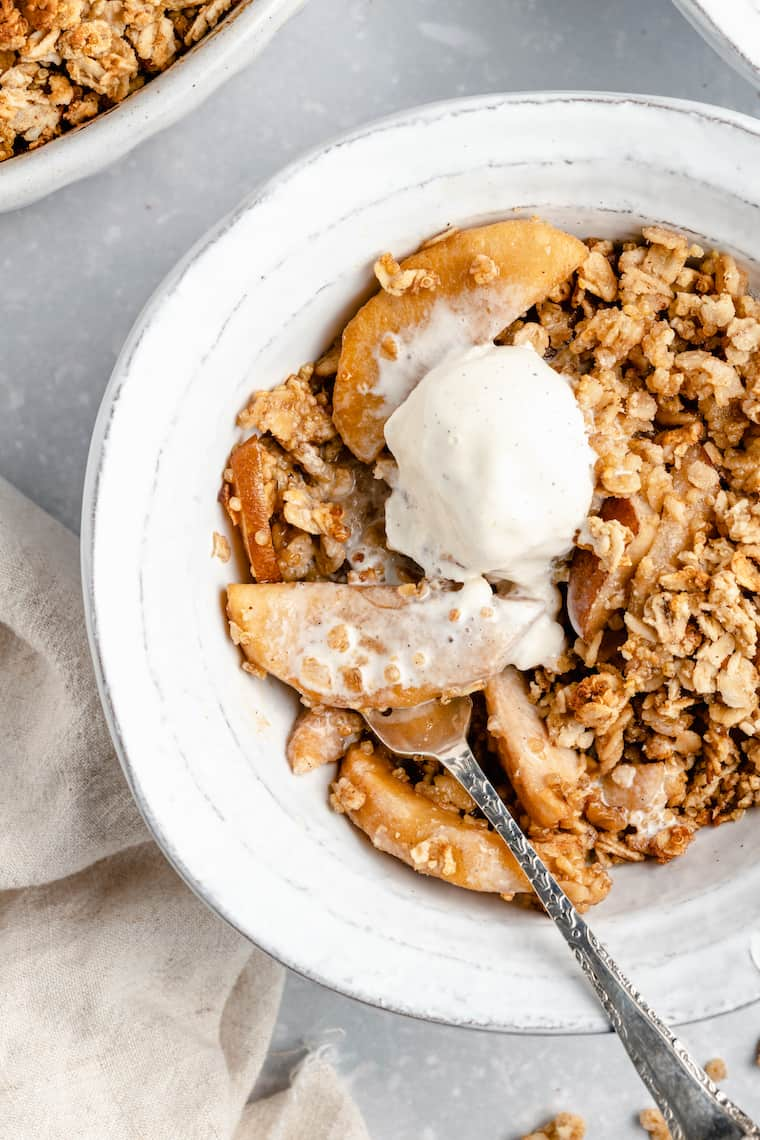 serving of vegan pear and apple crisp in a white ceramic bowl with ice cream