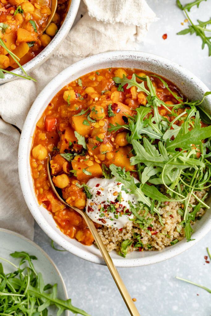 close up on a bowl of slow cooker chickpea soup with coconut yogurt, arugula and quinoa on top