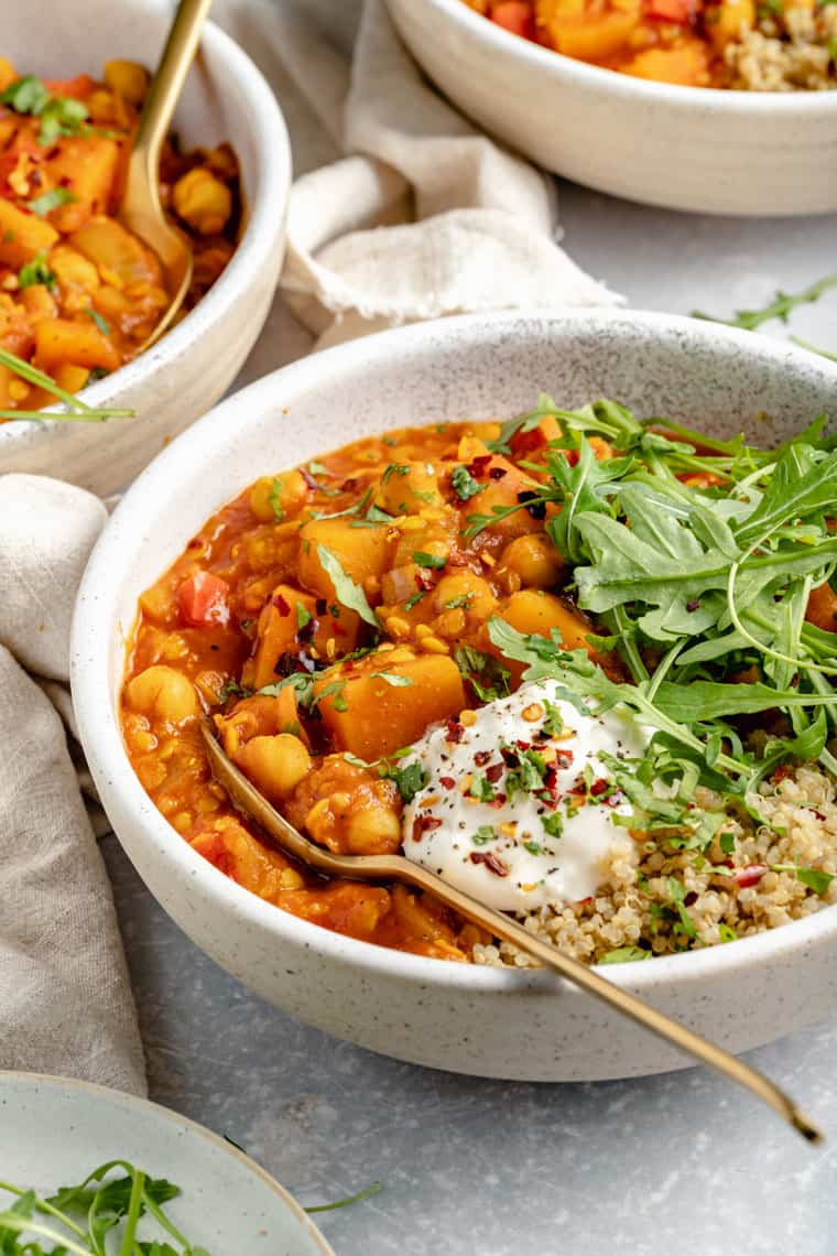 ceramic bowl with moroccan chickpea stew, qiunoa and arugula topped with vegan coconut yogurt