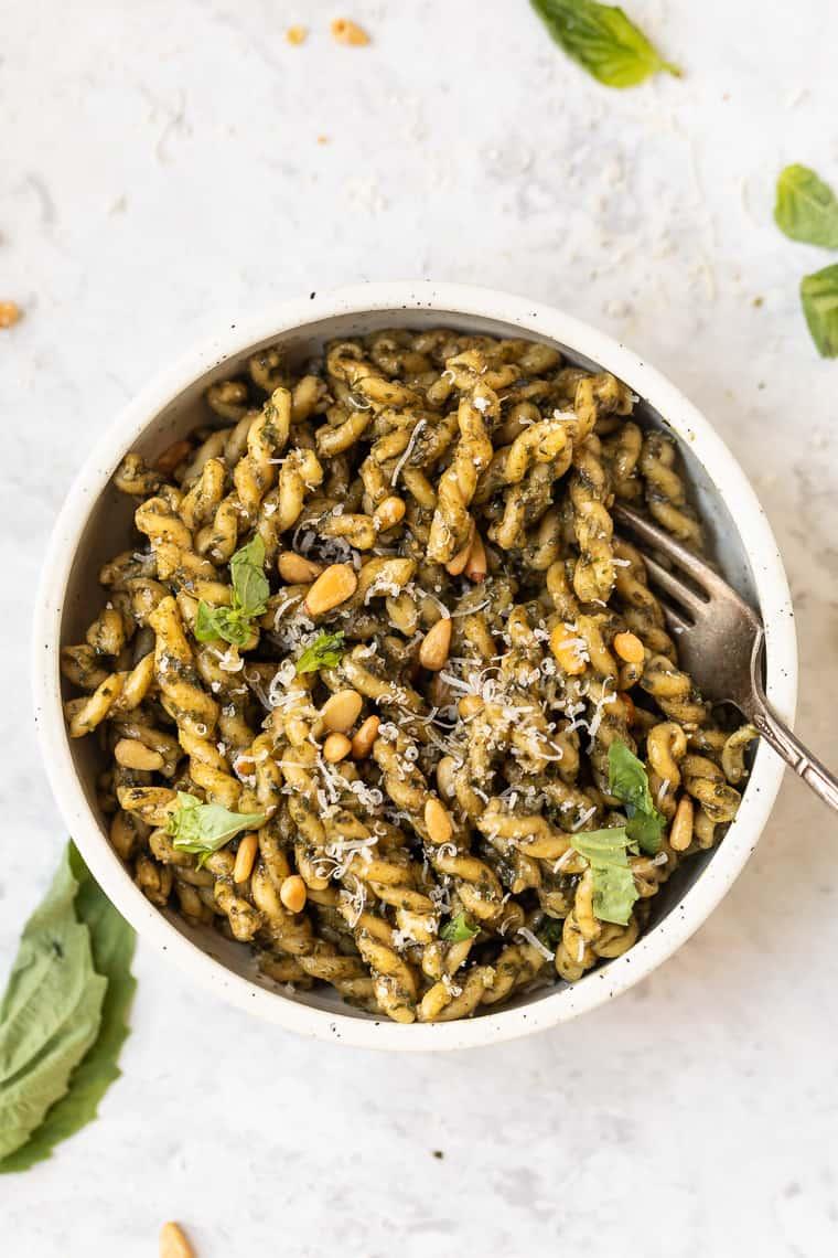 vegan pesto pasta with toasted pine nuts and vegan parmesan