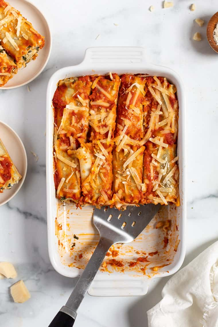 overhead of a white casserole dish with spinach lasagna roll ups and a metal spatula