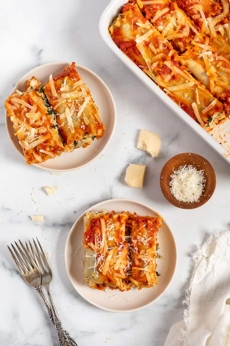 overhead of a table with plates of vegan lasagna roll ups and a baking dish with lasagna