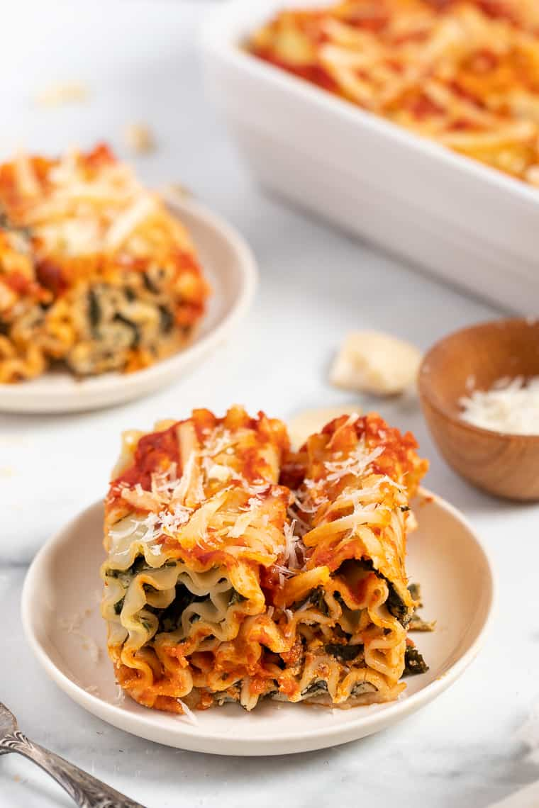 two vegan lasagna roll ups with spinach on a white plate