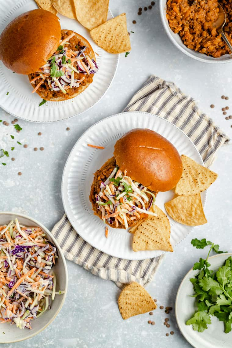 overhead of vegan lentil sloppy joes on hamburger buns with veggie slaw and tortilla chops on a grey background with a striped dishcloth