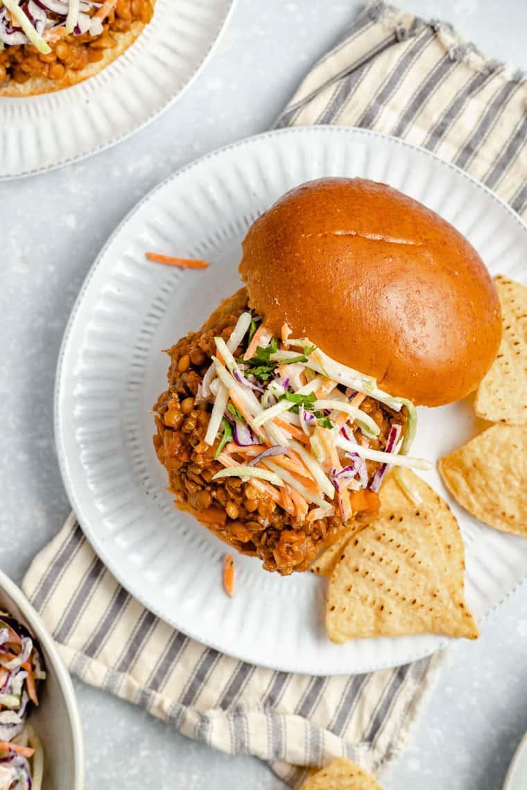 Close up overhead of a vegan lentil sloppy joe sandwich with tortilla chips and rainbow vegetable slaw on a hamburger bun