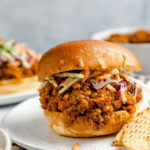 Vegan lentil sloppy joe sandwich on a hamburger bun with tortilla chips and vegetable slaw on a white plate with a stripped dishcloth