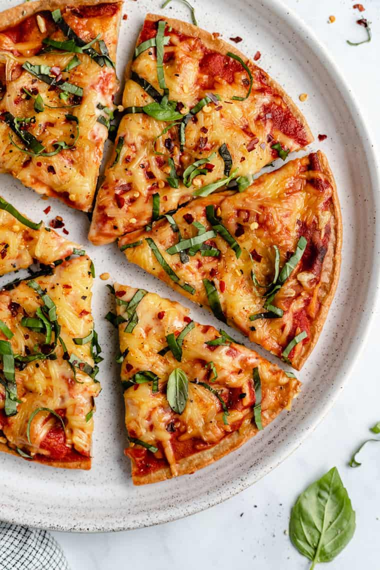 overhead of a plate with six slices of pizza made with quinoa crust and melted cheese with tomato sauce topped with fresh basil and red pepper flakes