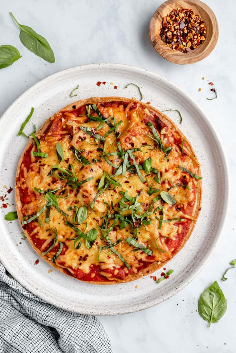 overhead of a whole pizza made with quinoa crust topped with tomato sauce, cheese and fresh herbs
