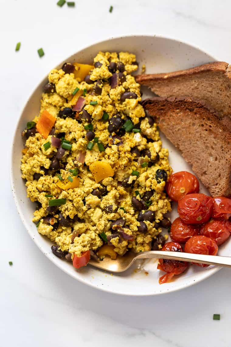 southwestern tofu scramble recipe on white plate with tomatoes and toast on the side