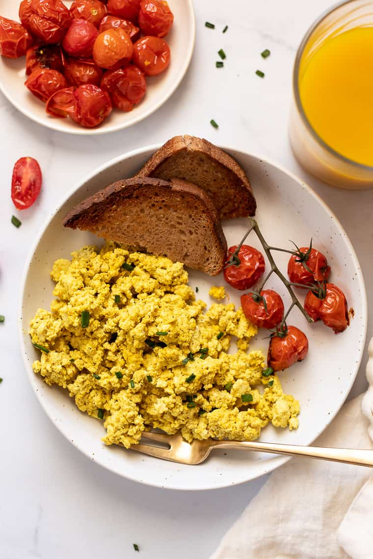 overhead of a white plate with basic tofu scramble with roasted tomatoes and two slices of wheat toast