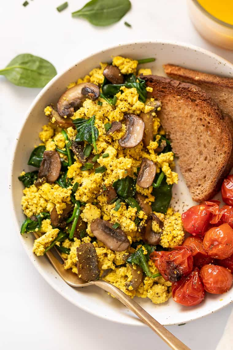 overhead of a white plate with mushroom and spinach tofu scramble with roasted tomatoes and two slices of wheat toast