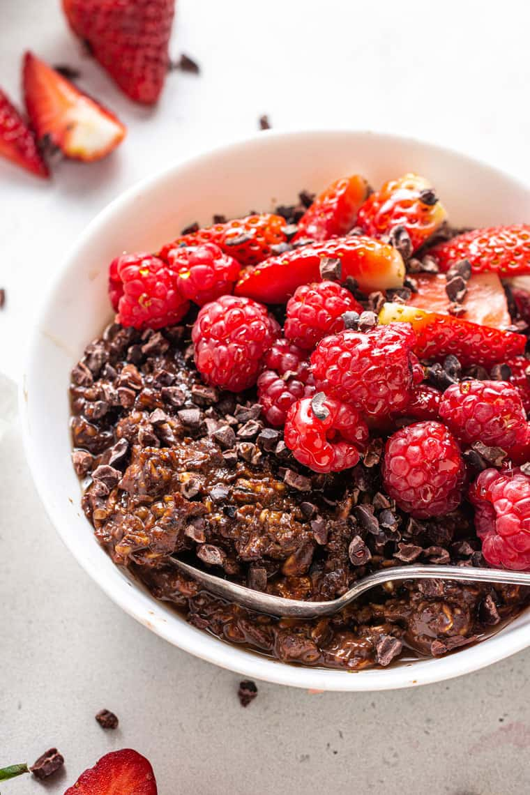 close up on a white bowl with chocolate protein oatmeal topped with fresh red berries