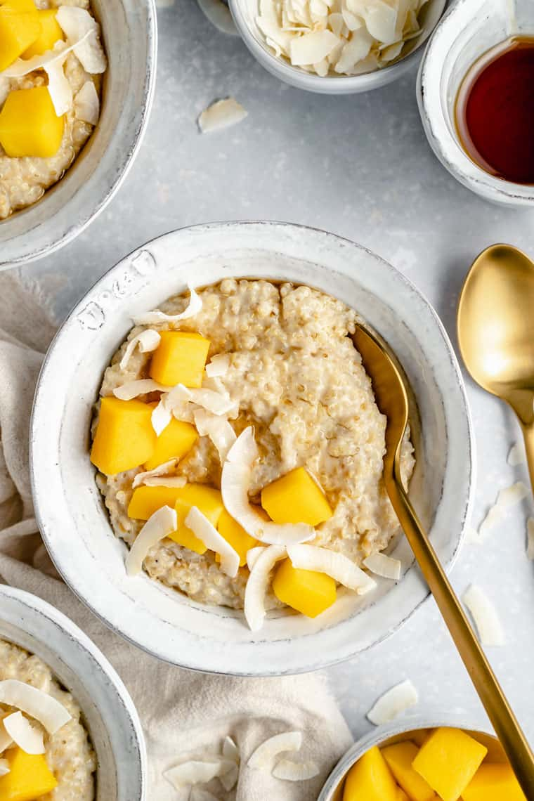 close up on a bowl of steel cut oats with coconut chips and mango cubes