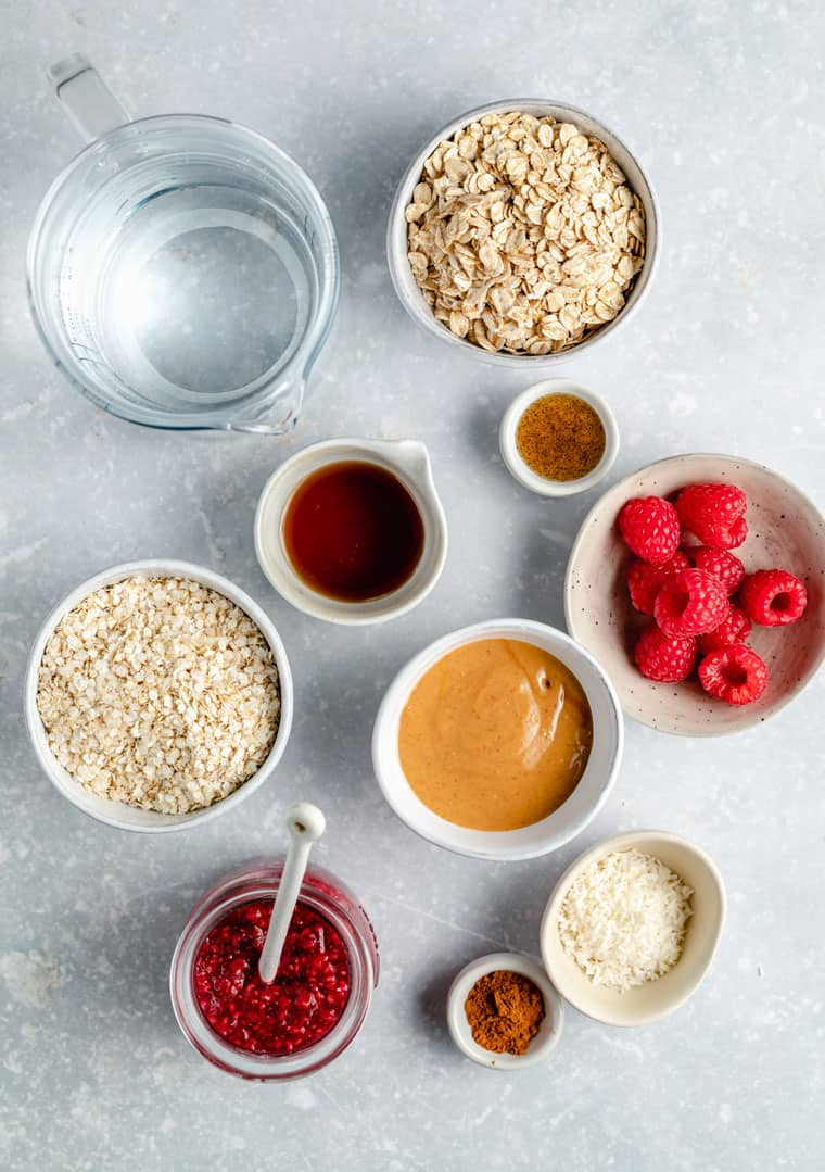 overhead of ingredients to make oatmeal with peanut butter, jam, water, berries, coconut, maple syrup and cinnamon