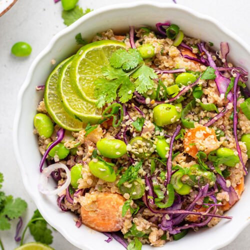 overhead of a white bowl with asian salad of quinoa, carrots, edamame, purple cabbage and lime