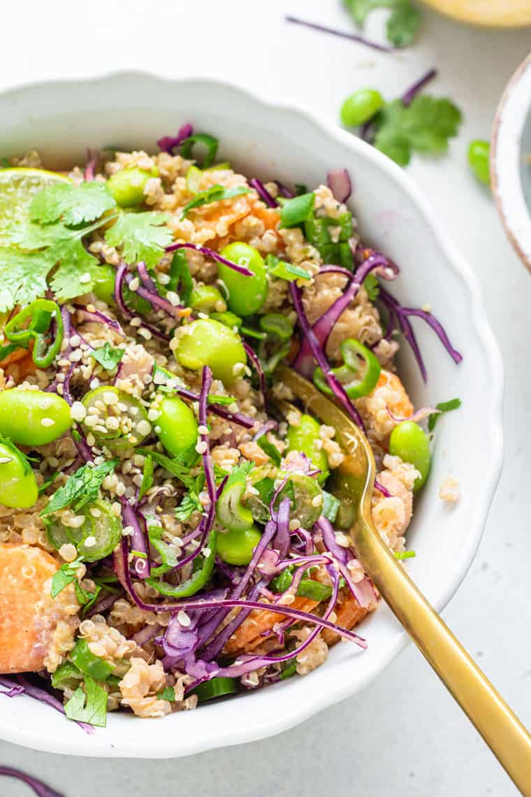 close up of a white bowl with vegetable quinoa salad with asian dressing