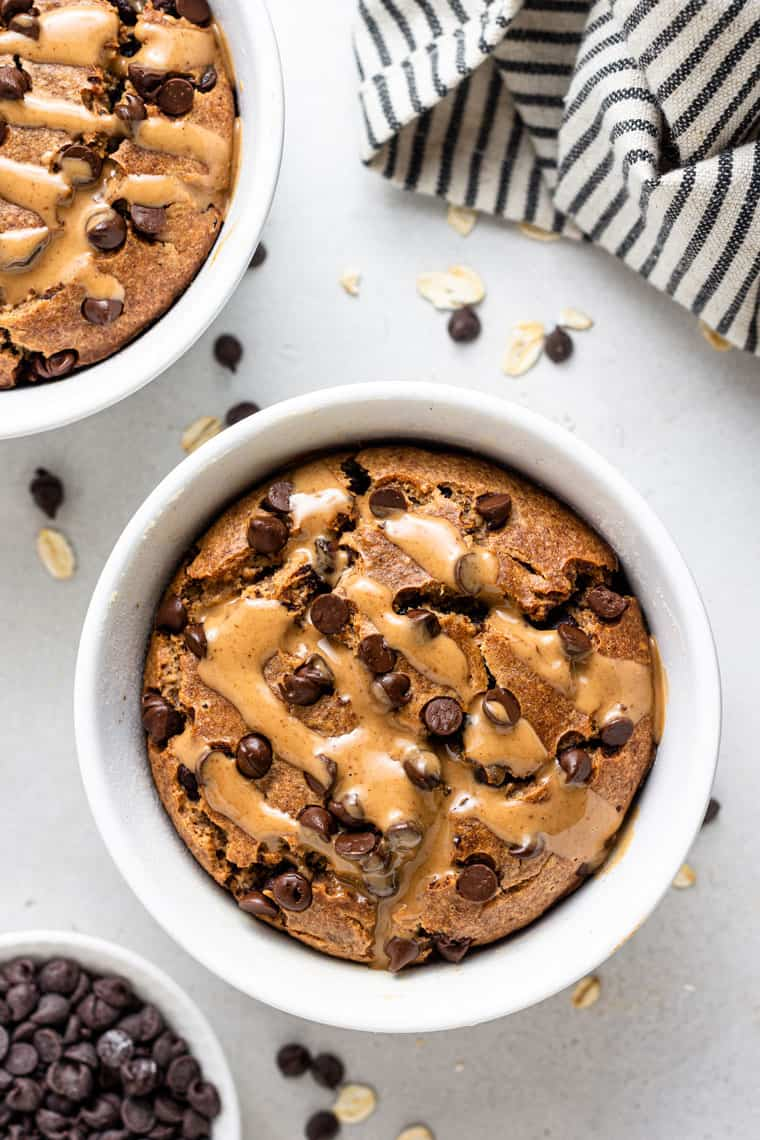 overhead of white bowl with blended vegan baked oatmeal topped with chocolate chips and almond butter